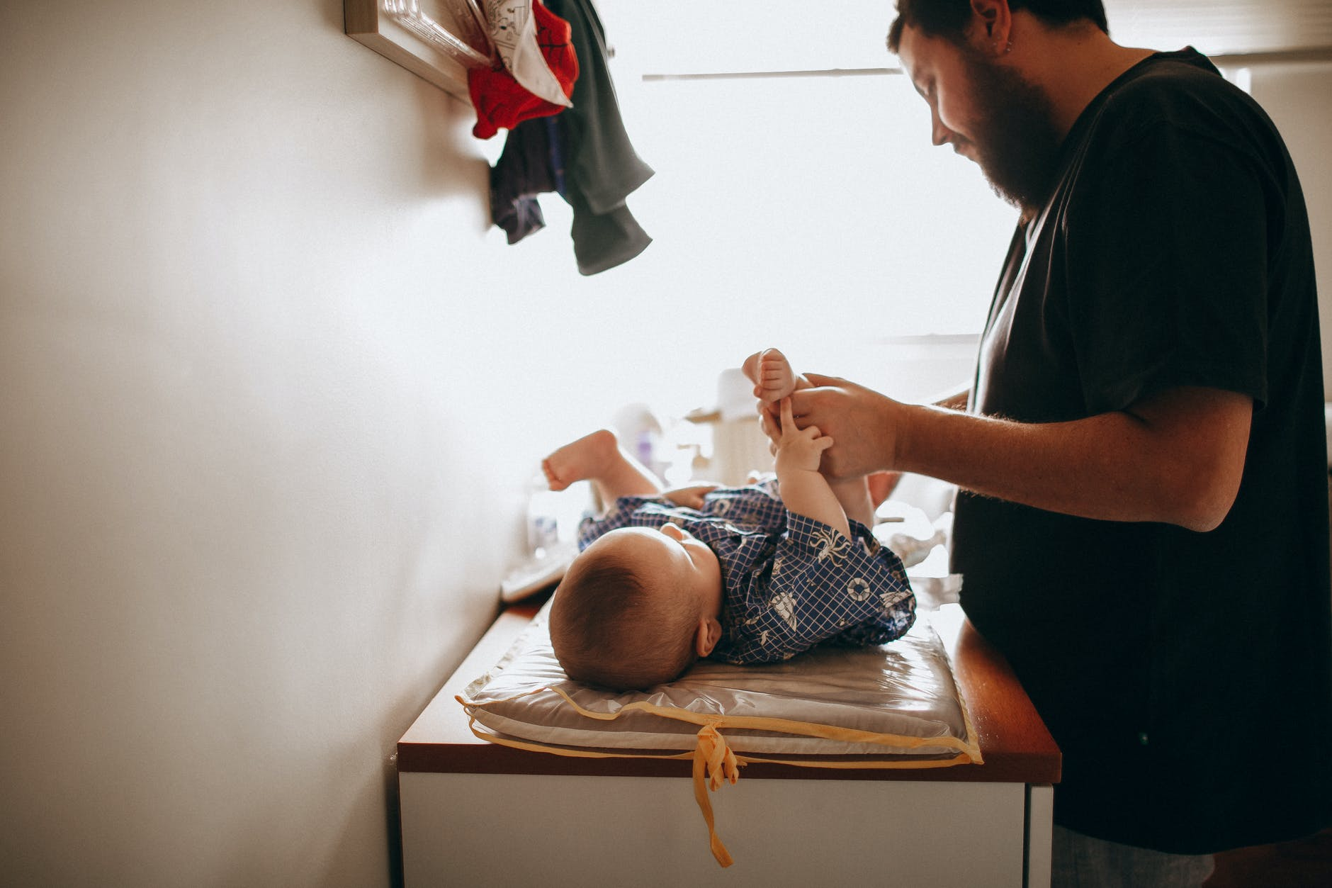 a father is changing his baby girl diaper
