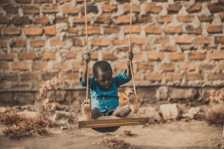 baby playing outside with a swing