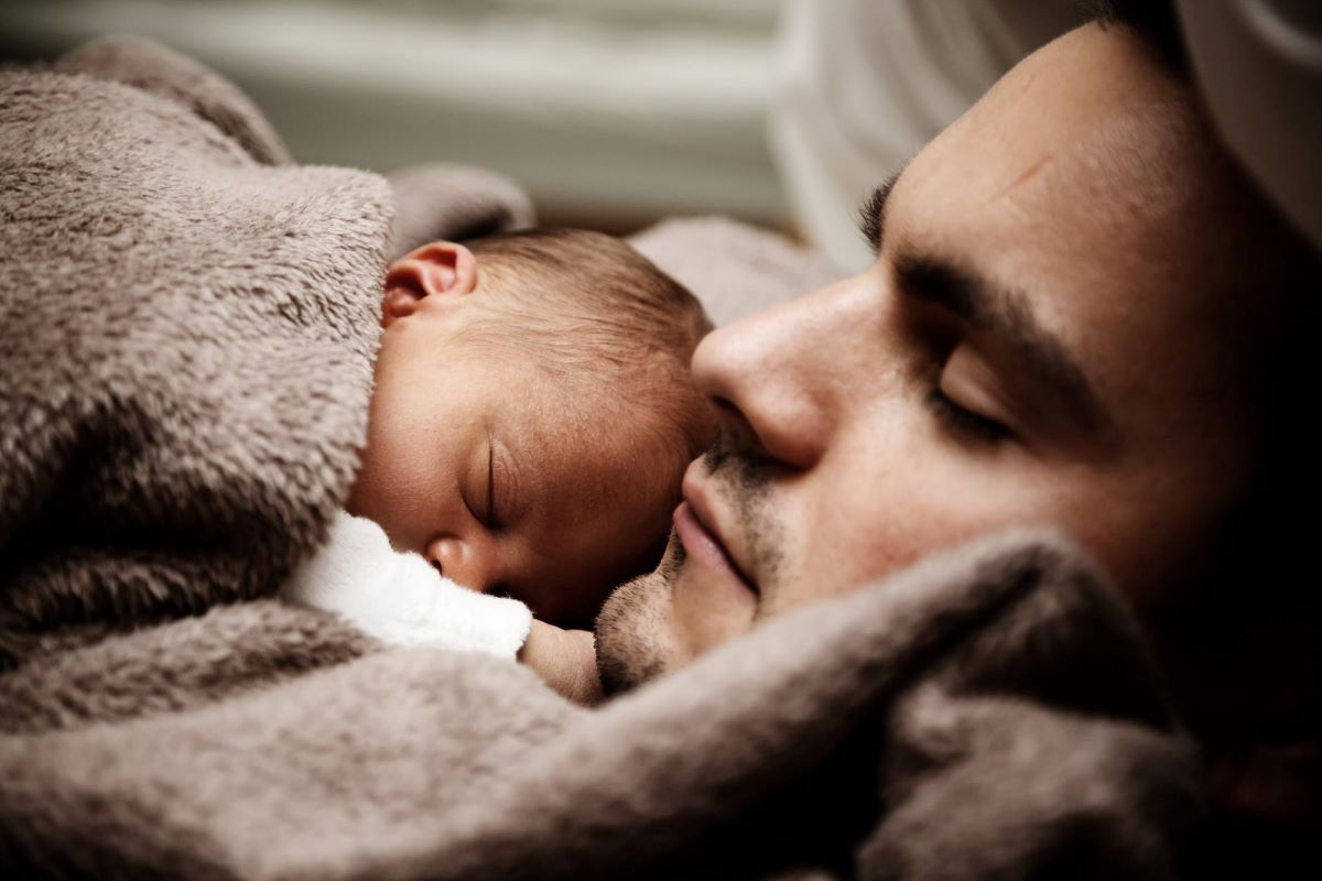 a dad holding his son while sleeping