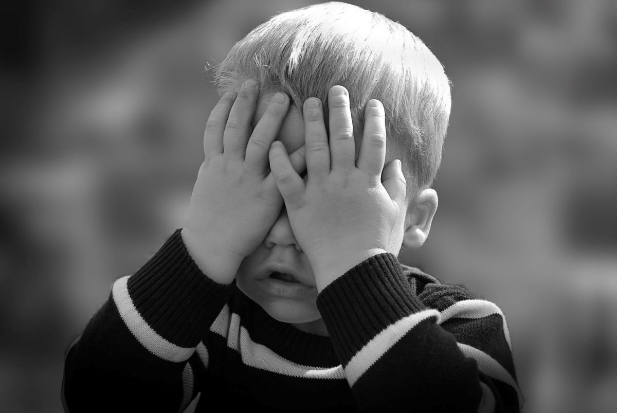 a toddler covering his face with both hands