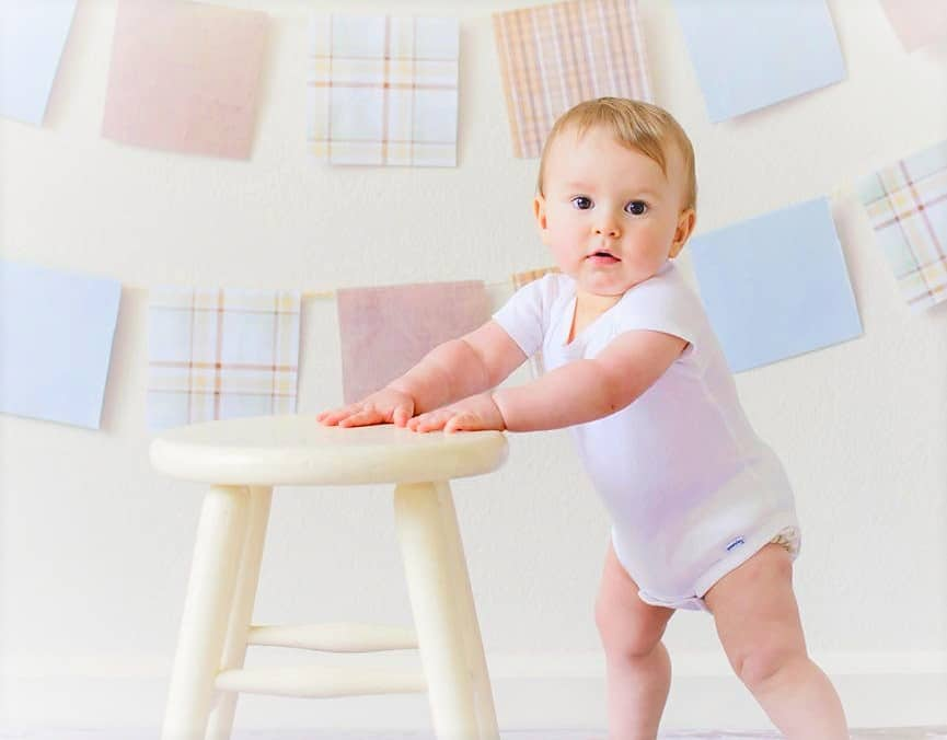 baby boy standing and holding a small chair