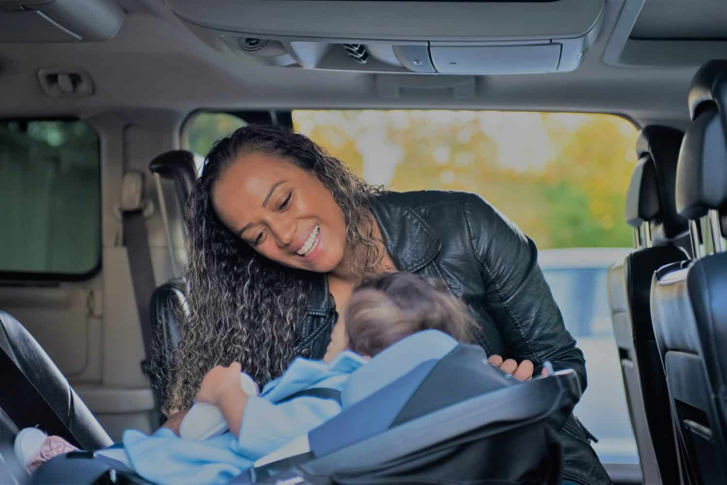 a mother puting her baby in the carseat