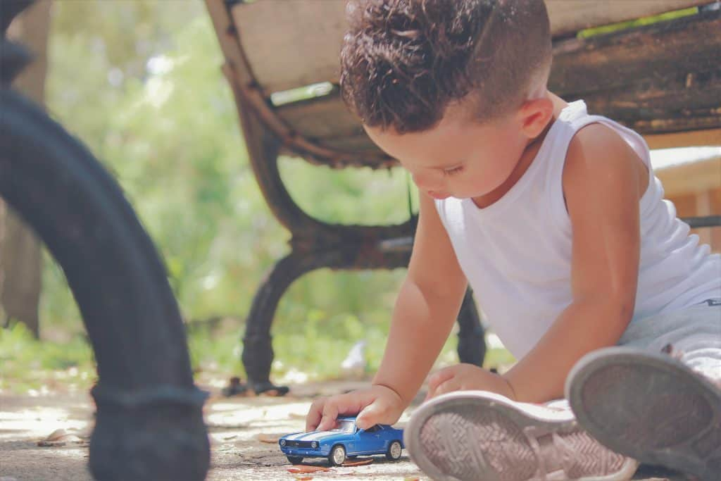little boy playing with a blue small car