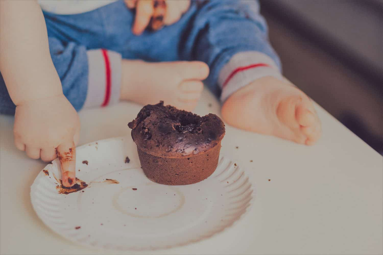 Baby trying to eat chocolate cupcake