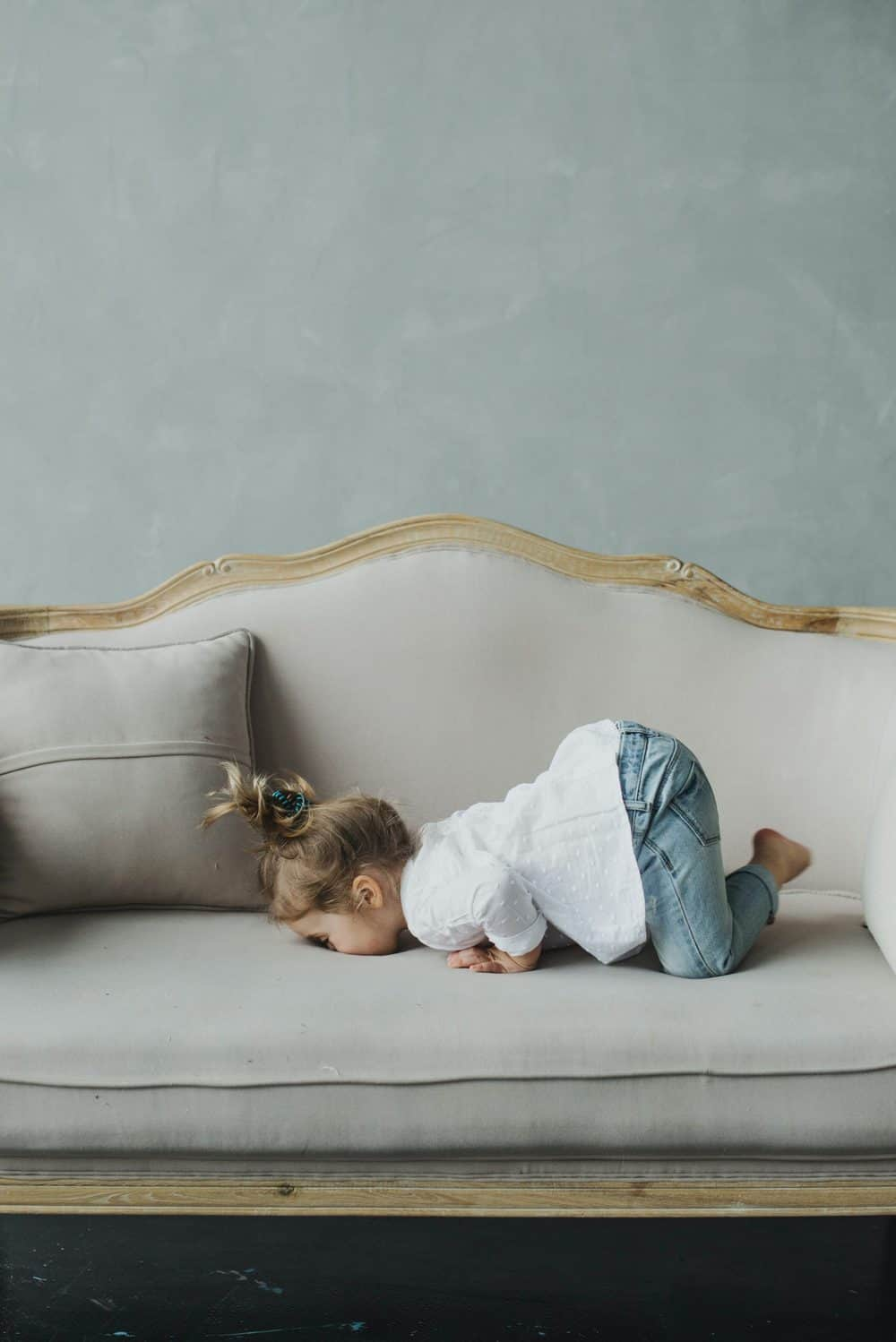 toddler girl laying in her face on a couch - comfortable
