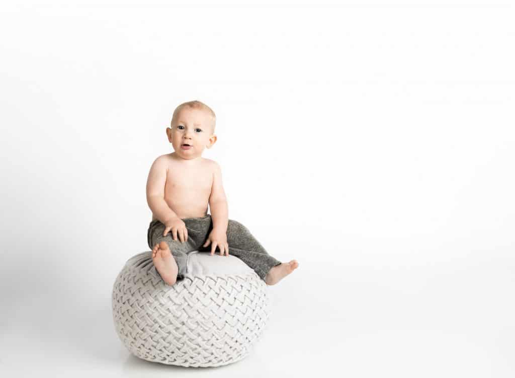 a toddler boy sitting on a round chair