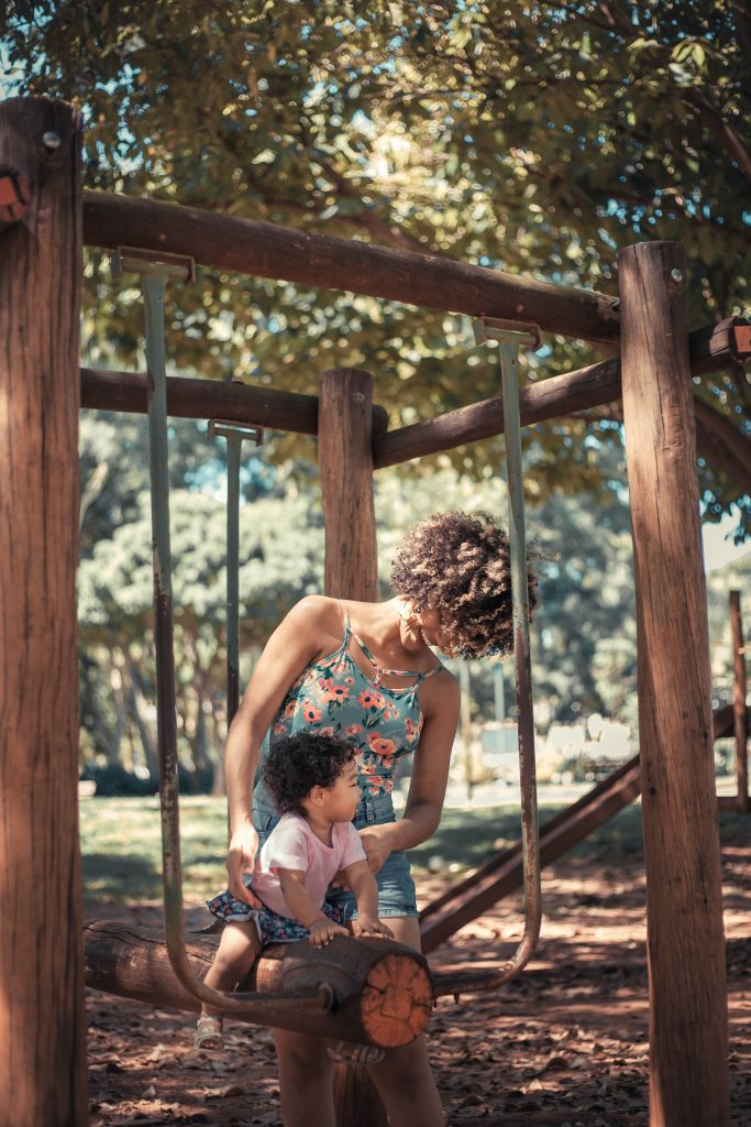 a mother playing outside with he daughter