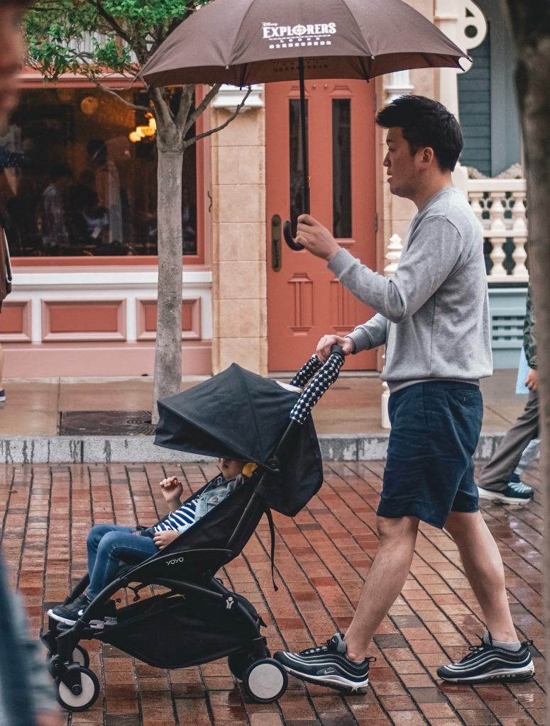 a father walking outside with his son in a stroller