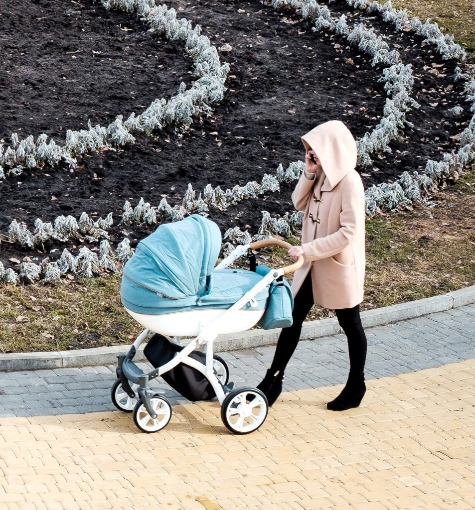 A mother walking with her baby in the stroller