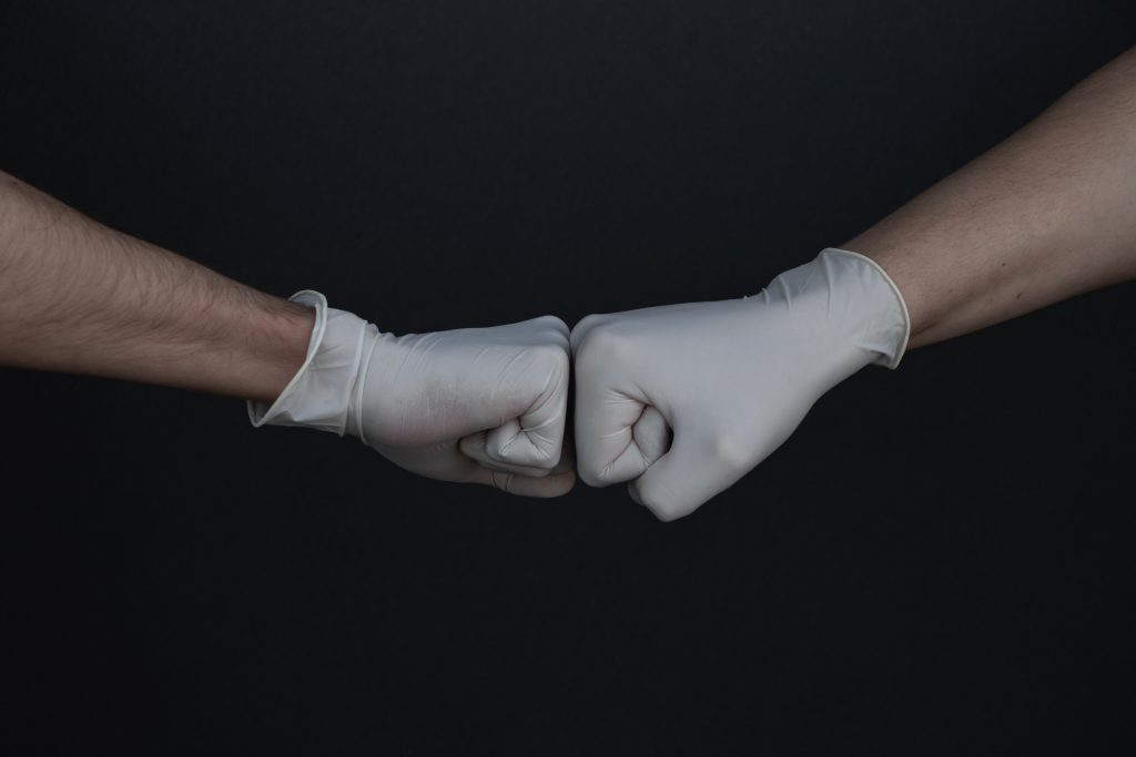 Two hands wearing disposable gloves