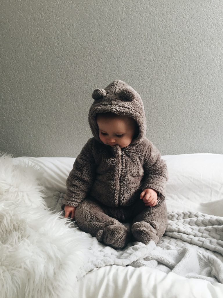 baby wearing a teddy outfit