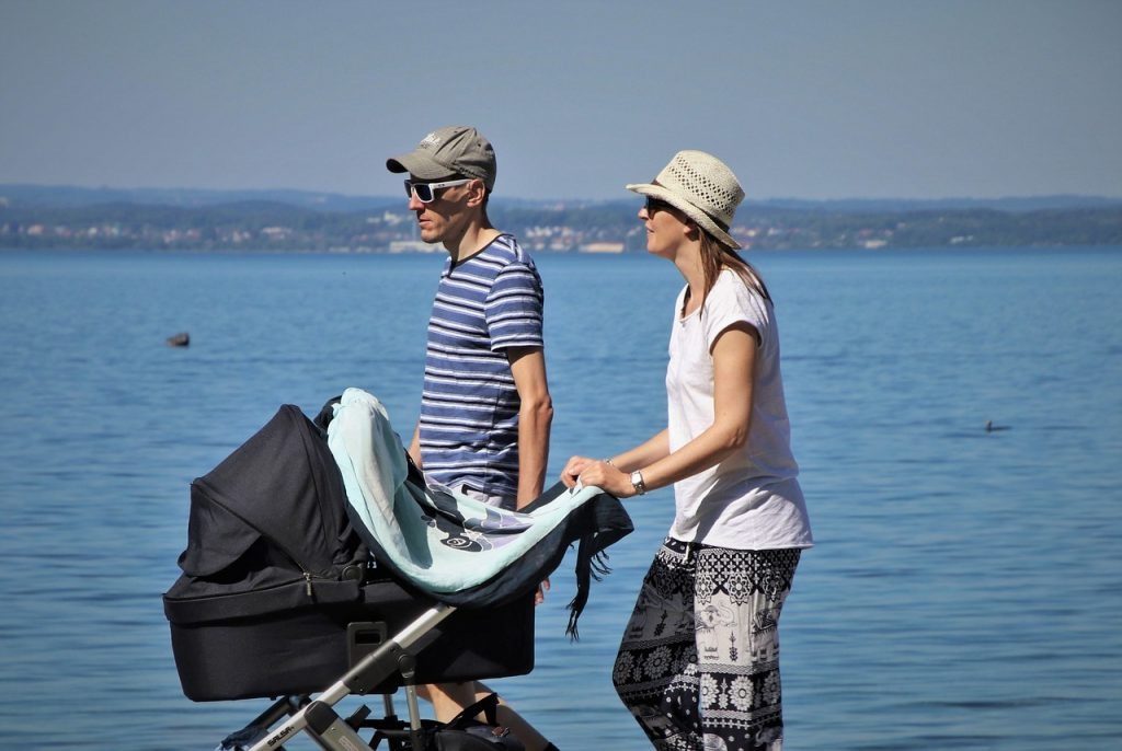 father and mother walking beside the water with their little one in the stroller
