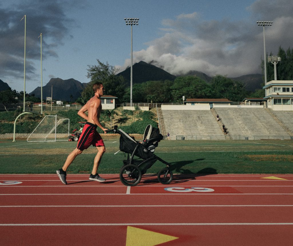Father running outside with a jogging stroller