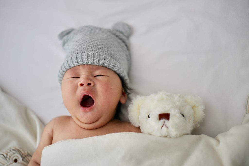baby sleeping next to his teddy