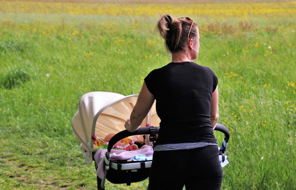 a mother pushing a double stroller