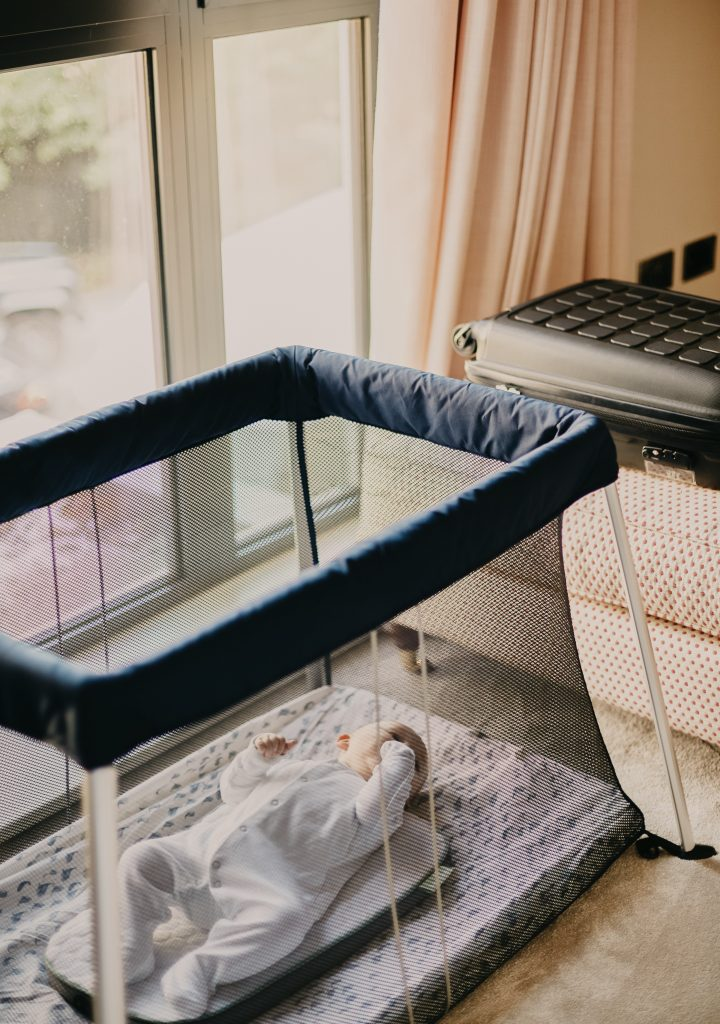 baby sleeping in a portable mesh bed