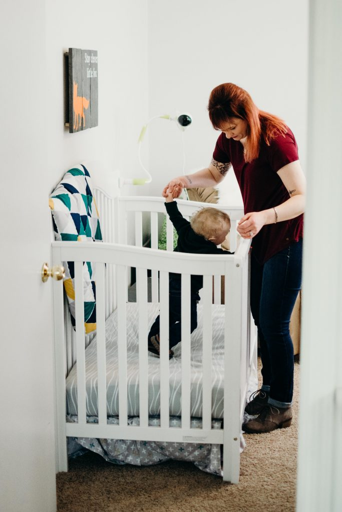 baby standing inside a white crib
