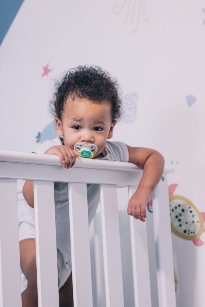 Toddler boy standing inside his crib with a pacifier in his mouth