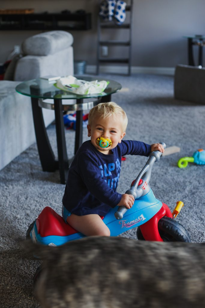 toddler boy setting on his bike inside the house