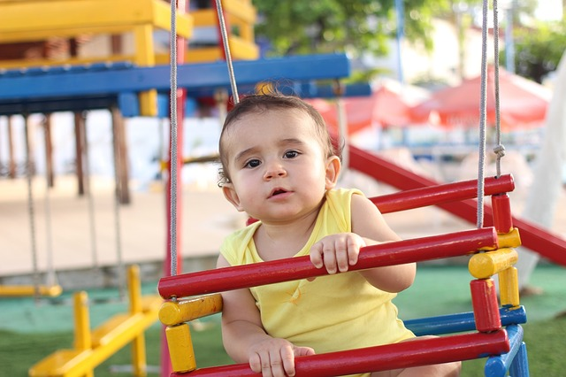 baby boy playing on a swing