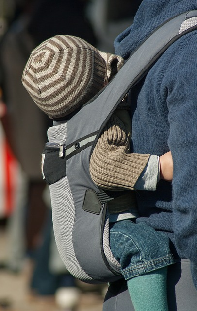 a toddler sitting in a baby carrier