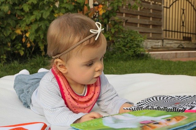 toddler girl doing tummy time and looking at a sensory toy