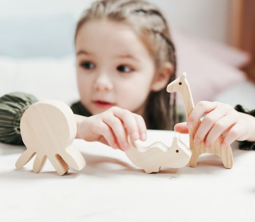 toddler girl playing with wooden toys