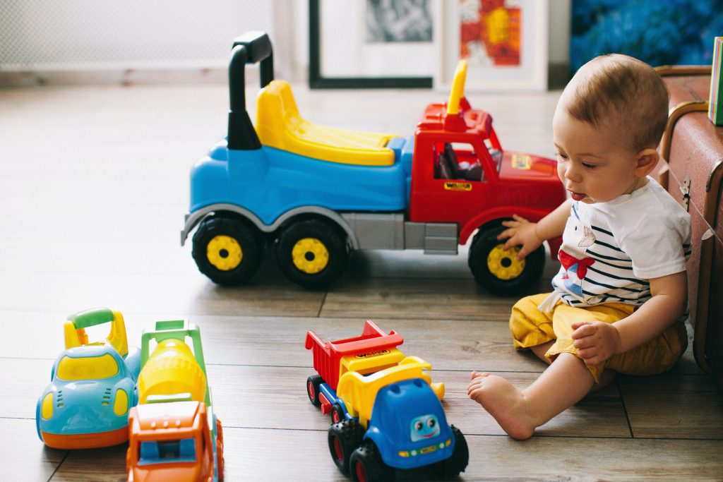 toddler boy playing with his toy trucks