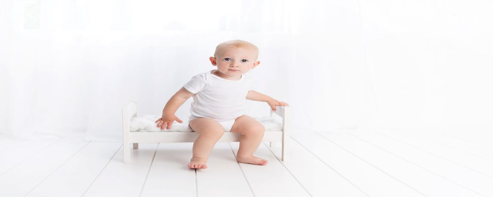 a toddler boy sitting on a small bed